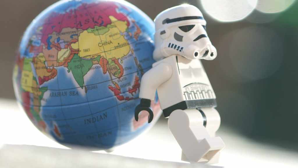 Star Wars lego minifigure leaning on small globe of earth